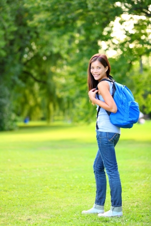 Student girl portrait wearing backpack outdoor in park smiling happy going back to school. Asian female college or university student in full length. Mixed race Asian  Caucasian young woman model.