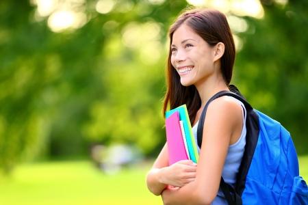 大学大学生の女の子探して幸せな本やキャンパス公園でノートに笑みを浮かべてします。美しい若い混合レース アジア中国白人若い女性女性モデ