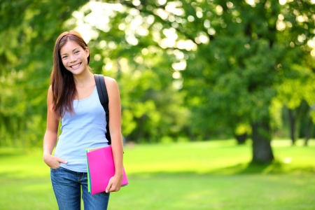 Student girl portrait holding books wearing backpack outdoor in park smiling happy going back to school. Asian female college or university student. Mixed race Asian  Caucasian young woman model.