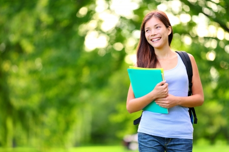 Student girl outdoor in park smiling happy going back to school. Asian female college or university student. Mixed race Asian  Caucasian young woman model wearing school bag holding books. photo