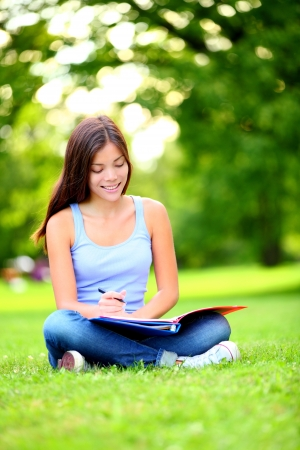 Student girl studying in park. Happy young asian adult student sitting writing and reading outdoor on university campus park. Mixed race Chinese Asian  Caucasian female student working. photo
