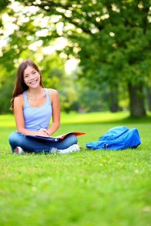 Student girl studying in park going back to school at university college. Happy student sitting studying, writing and reading outside. Multi ethnic Chinese Asian  Caucasian female student woman