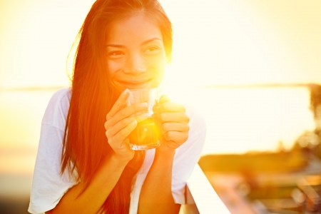 tea house: Asian woman drinking coffee in sun sitting outdoor in sunshine light enjoying her morning coffee. Smiling happy multiracial female Asian Chinese  Caucasian model in her 20s. Stock Photo