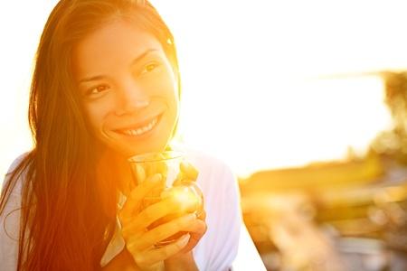 그녀의 아침 커피를 즐기는 태양 빛에 야외 앉아 햇빛에 커피를 마시는 여자. 행복 한 미소 Multiracial 여성 아시아  백인 모델. 스톡 콘텐츠