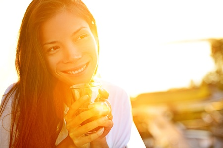 Woman drinking coffee in sunshine sitting outdoor in sun light enjoying her morning coffee. Smiling happy multiracial female Asian Chinese  Caucasian model in her 20s. Banco de Imagens