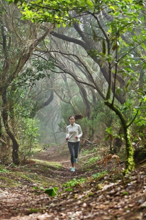 Runnerwoman cross-country running in beautiful forest trail run. Female athlete jogger training outdoor in amazing atmospheric forest nature landscape. Fit female fitness model with healthy lifestyle. photo