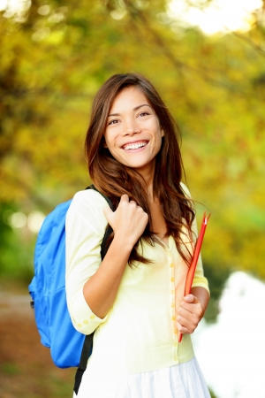 high school: Asian student girl back to school university. Beautiful woman holding books in autumn background. Asian student girl on university college campus park smiling happy. Mixed race Asian Caucasian girl.