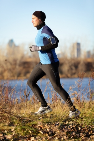 armband: Running man jogging in autumn listening to music on smart phone. Runner training in warm outfit on cold day. Fit male fitness athlete model training outdoor in fall. Full body length of jogger. Stock Photo