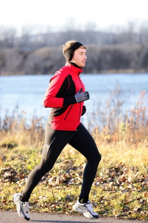 Running man jogging in autumn outdoor on cold day wearing long tights and sporty jogging outfit. Fit male fitness athlete model training outdoor in fall. Full body length of jogger.