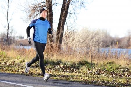 sentier: Homme homme de coureur courant de l'automne, le jour froid porter des collants longs et costume de jogging sportive longtemps. Monter athl�te masculin mod�le ext�rieur de formation de remise en forme � l'automne. La longueur du corps plein de jogger.