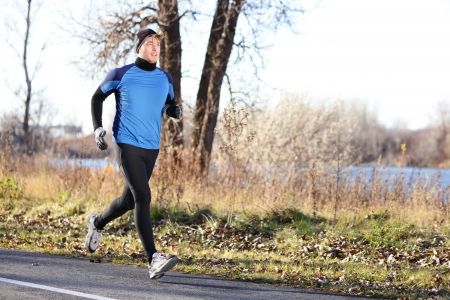 Male runner man running in autumn on cold day wearing long tights and long sporty jogging outfit. Fit male fitness athlete model training outdoor in fall. Full body length of jogger. photo