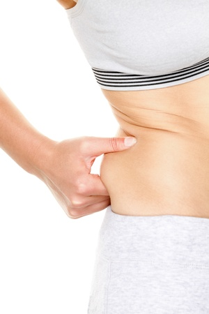 gaining: Weight gain - woman gaining weight touching fat pinching waist. Female med-section close up isolated on white background. Young female model in weight loss conceptual image. Stock Photo