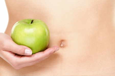 Apple fruits and stomach health concept. Eating healthy apple fruits is good for stomach digestion and health. Woman showing green apples in close up of belly stomach. photo