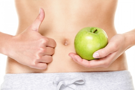 Eating healthy apple fruits is good for stomach digestion and health. Woman showing green apples and thumbs up hand sign in close up of belly stomach. Stock Photo