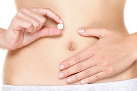 birth control: Pastillas anticonceptivas, p�ldoras anticonceptivas, p�ldoras de vitamina, p�ldoras para una mejor digesti�n o pastillas contra el dolor menstrual. Mujer que sostiene la tablilla blanca delante de est�mago. Close up.