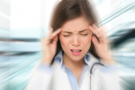 Migraine and headache people - Doctor stressed. Woman Nurse  doctor with migraine headache overworked and stressed. Health care professional in lab coat wearing stethoscope at hospital.