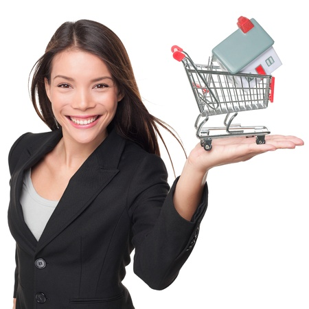 realtor: Real estate agent selling home holding mini house in shopping cart. Female realtor in business suit showing model house smiling happy isolated on white background. Multiracial Asian woman agent.