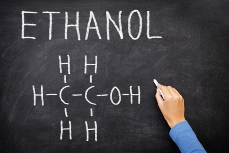 ethanol: Ethanol alcohol chemical molecule structure on blackboard. Science teacher or chemistry student drawing chemical formula on blackboard in class. Stock Photo