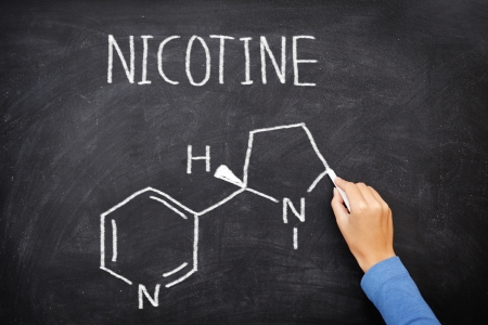 nicotine: Nicotine molecule chemical structure on blackboard. Chemical structure of nicotine from cigarettes written on blackboard by teacher in education of health. Nicotine molecule on green chalkboard. Stock Photo