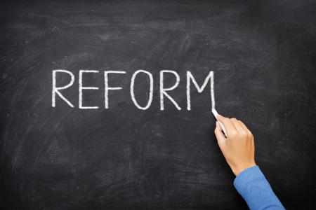 Reform blackboard - education reform or other. Hand writing REFORM with chalk on black chalkboard.