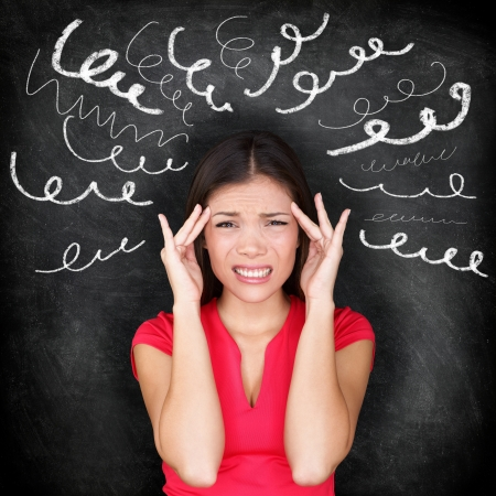 stress test: Stress - woman stressed with headache. Female stressed and worried with migraine headache pain. Blackboard concept with young female model on chalkboard black background. Asian Chinese  Caucasian.