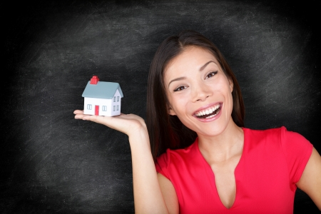 loaning: New house owner woman happy - blackboard concept. Woman showing mini house model.