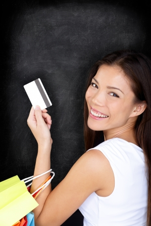 happy shopper: Shopping woman with credit card on blackboard holding shopping bags on blackboard background. Shopper girl on black chalkboard background with copy space. Multiracial Asian model.