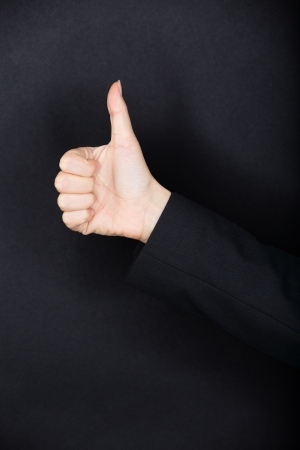 uphold: Person in dark clothing giving a Thumbs up gesture of approval and success against a dark studio background with copyspace. Black texture background..
