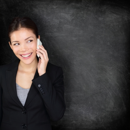 Smart phone blackboard, Woman on mobile phone looking at chalkboard sign showing copy space for your text or design. Business woman in suit talking smiling happy on smartphone, Asian Caucasian female. photo