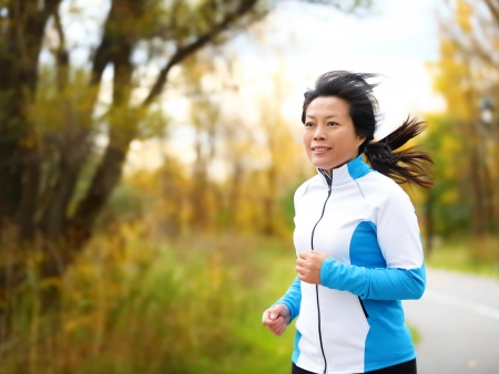 Active woman in her 50s running and jogging. Middle aged Asian mature female jogger outdoor living healthy lifestyle in beautiful autumn city park in colorful fall foliage. Asian Chinese adult in her fifties.