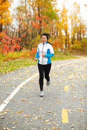 Middle aged woman running active in her 50s. Mature female jogging outdoor living healthy lifestyle in beautiful autumn city park in colorful fall foliage. Asian Chinese adult in her fifties. photo