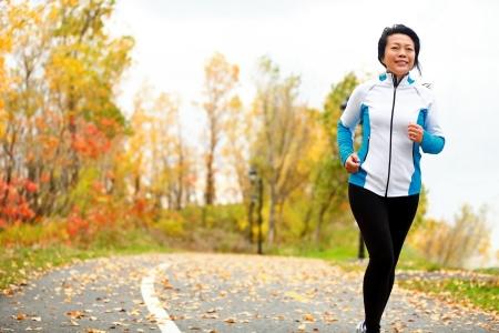 Volwassen Aziatische vrouw draait actief in haar jaren '50. Middelbare leeftijd vrouwelijke jogging outdoor living gezonde levensstijl in de herfst prachtig stadspark in kleurrijke bladeren vallen. Aziatische Chinese volwassen in haar jaren vijftig. Stockfoto