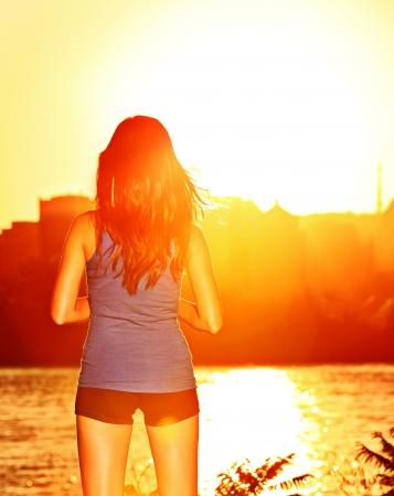luz do sol: Mulher que aprecia a luz do sol pôr do sol depois de correr e treinar ao ar livre. Menina desportiva desfrutando de belas sunshine relaxar fora depois do treino.