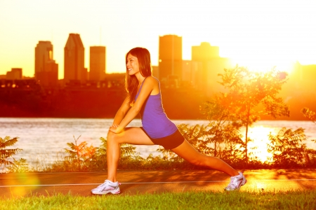 warm up exercise: Woman runner stretching legs after running training in sunshine at sunset. Fit female jogger athlete training outside in Montreal, Canada, Quebec. Stock Photo