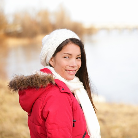 warm clothing: Fall woman enjoying late autumn  winter at lake. Portrait of beautiful happy smiling asian girl looking at camera wearing warm clothing and scarf outdoor. Multiracial Asian Caucasian female model.