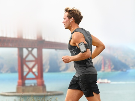 earbud: Running man - male runner in San Francisco listening to music on smart phone. Sporty fit young man jogging by San Francisco Bay and Golden Gate Bridge. Jogger listening to training music on smartphone Stock Photo