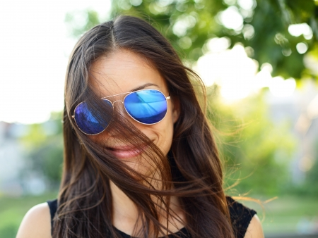 Sunglasses woman funky portrait outdoor with hair flying. Young girl wearing colored sunglasses outside looking at camera smiling happy, Young cool modern multiracial female model girl in her 20s, photo