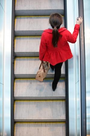 Urban mensen - vrouw commuter lopen op roltrap trap in de stad. Hoge hoek mening perspectief van bovenaf toont jonge vrouwelijke professionele woon-werkverkeer te werken. Stockfoto