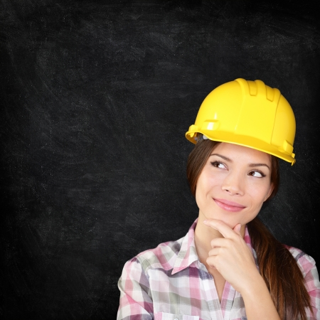 Woman architect, engineer, surveyor or construction worker wearing protection hardhat thinking looking thoughtfully to the side on chalkboard blackboard texture for copy space. photo