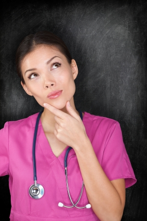 school nurse: Female medical doctor nurse thinking by blackboard. Woman medical professional looking thinking at empty chalkboard copy space. Multiracial Asian Caucasian nurse in pink scrubs. Stock Photo