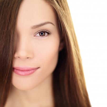 Haarverzorging schoonheid vrouw met lang haar. Vrouwelijke brunette schoonheid en haar behandeling close-up. Gemengd ras Aziatische Chinees  Kaukasische vrouwelijke model in haar 20s geïsoleerd op een witte achtergrond.