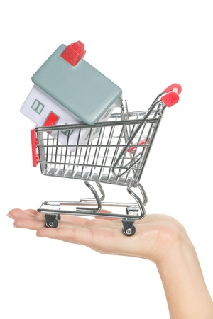House and home for sale in shopping cart concept. Hand showing mini model house in miniature shopping cart. Buying new house, real estate and home mortgage conceptual image isolated, white background. photo