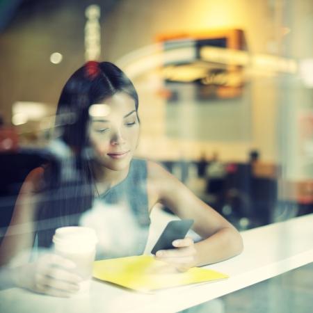 estilo de vida: Cidade Cafe lifestyle mulher no telefone de beber mensagem de texto mensagens de texto café no aplicativo de smartphone que senta-se no interior badalado Cafe urbana. Modelo novo fresco moderno raça mista fêmea caucasiano asiático de 20 anos.