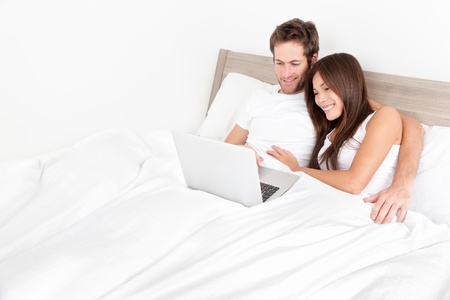 Bed couple happy on laptop computer in bedroom. Young couple watching movie together on laptop before sleeping. Multiracial couple, Asian woman, Caucasian man at home. photo