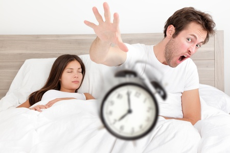 Wake up - couple waking up early throwing alarm clock. Funny bed concept with young interracial couple waking up late. Man throwing alarm clock, and woman sleeping. Asian female, Caucasian male models photo