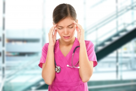 hospital stress: Stressed female nurse medical professional with headache. Portrait of woman nurse having migraine pain being overworked having stress at health care hospital.