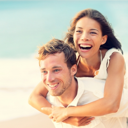 Having Fun: Love - Happy couple on beach having fun piggyback ride outdoor smiling happy laughing together on romantic holidays vacation travel trip. Young multiracial people, Asian woman, Caucasian man, 20s.