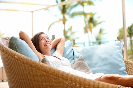 ソファの女性を楽しむ贅沢なライフ スタイル屋外日夢を見てリラックスと陽気な笑顔を幸せそうに見えて思考。美しい若い多文化アジア白人彼女の