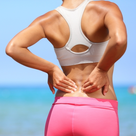 Back pain - woman having painful muscle injury in lower back. Fitness girl sport girl with sports injury outdoor on beach. Stock Photo