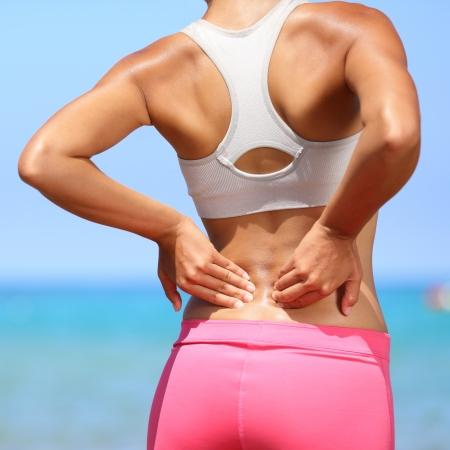 dolor de espalda: El dolor de espalda - mujer que tiene una lesi�n muscular dolorosa en la espalda baja. Fitness girl chica deportiva con lesi�n deportiva al aire libre en la playa.